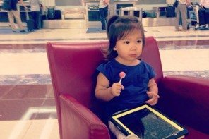 Layla waiting patiently with lollipop and iPad as Emirates stuffs up yet agai