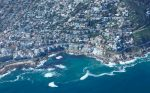 Birds eye view of residential neighbourhoods and clear blue waters of the Indian Ocean.