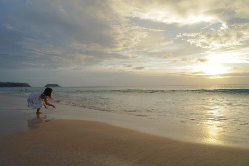 Little girl dances with the ocean as the sun sets in Karon Beach, Phuket